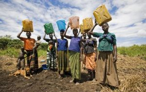 Women in Uganda carrying water from a shallow well  in plastic jerricans