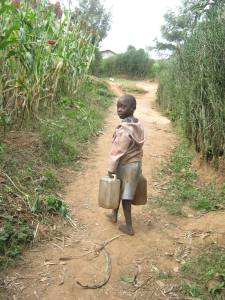 A young girl in Kabale district of Uganda returns home after collecting water from a shallow well