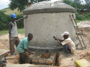 Adequate resources such as these men constructing a water tank are needed to sustain routine operation and maintenance of existing WASH systems and services