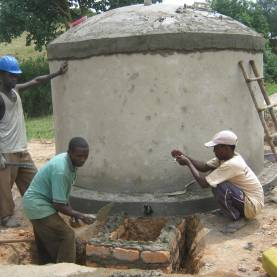 Men in rural part of Uganda constructing a rainwater harvesting tank