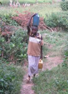 A girl child returns from collecting water in a shallow well in western Uganda.