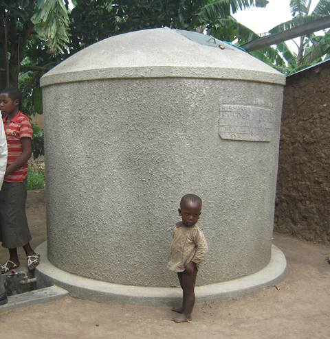 A kid stands close to a water tank. Rainwater tanks are vital in water harvest and storage
