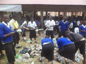 Students of Mwizi Secondary School in Mbarara district stuff plastic bags into the plastic bottles meant to be used in construction of their school's library