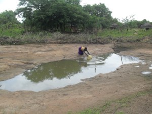 Acan fetches water from an Inselberg in Kitgum