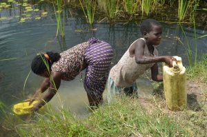 Evelyn Nimusiima and her sister fetch water from a well in Rwenshanku, Bubaare parish in Uganda's southwestern district of Mbarara. Water availability and sustainability is dependent on the way catchment areas are managed and subsequently how surface water is recharging deeper into the soil so that it can be retained by the aquifers. And yet, most water users in developing countries seem not to know this. Photo by Tushabe Andrew