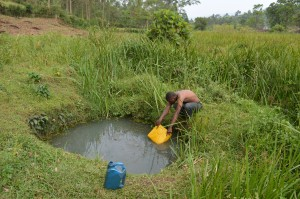 Chrispus Twikirize, fetches water from their well in Ibaare, Igara Bushenyi district of Uganda