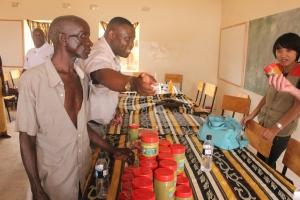 Kafweku (C) seems to be telling visitors the signficance of Moringa as Chiponda (L) looks on
